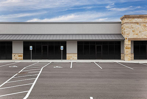 A blank, generic strip mall against a blue sky with an empty parking lot.